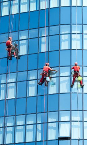 86751573 - five workers washing windows in the office building